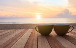 tasse-de-caf-sur-la-table-en-bois-au-coucher-du-soleil-ou-la-plage-de-lever-de-soleil-61375485