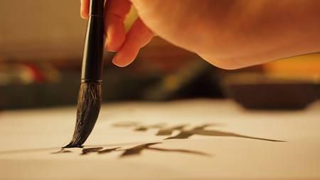 33112584-gros-plan-sur-la-main-tenant-l-écriture-de-calligraphie-au-pinceau